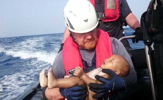 Drowned migrant baby in the arms of a German rescuer